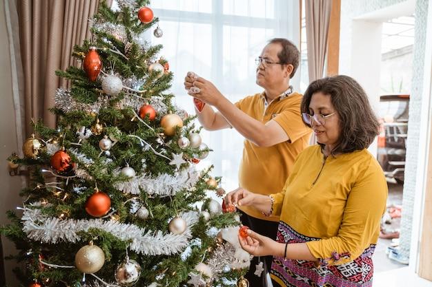 自宅でクリスマスツリーを飾る成熟したカップル