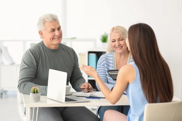 Пожилая пара обсуждает пенсионный план с консультантом в офисе