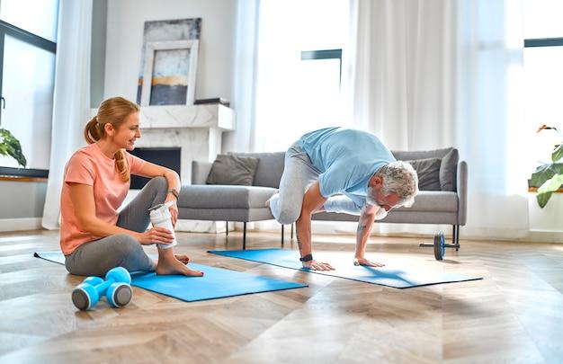 Пожилая пара делает упражнения или йогу дома и весело.
