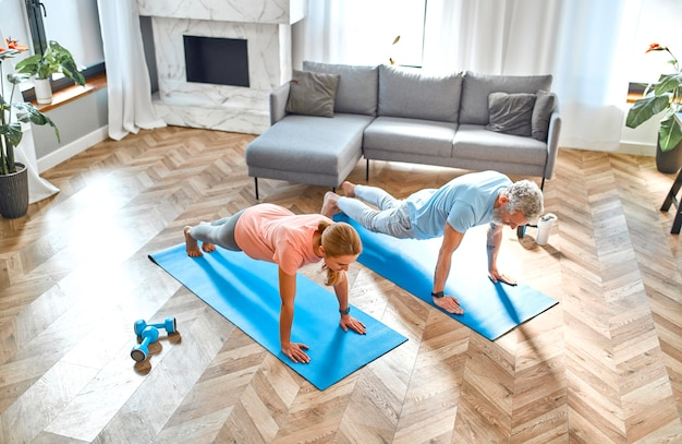 Пожилая пара занимается дома упражнениями или йогой.