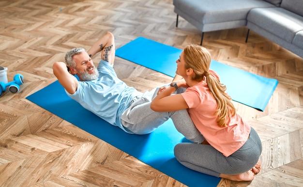 Пожилая пара делает упражнения дома и развлекается.