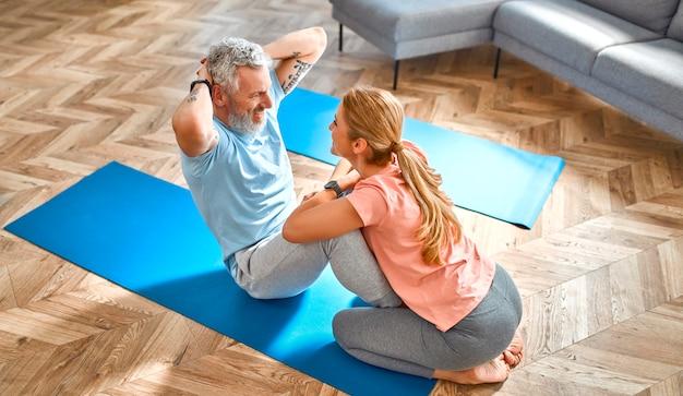 自宅で運動をして楽しんでいる成熟したカップル。