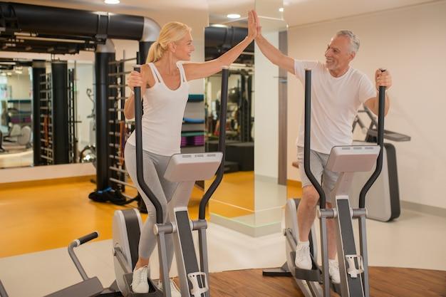 Пожилая пара вместе тренируется в тренажерном зале и ощущает прилив энергии