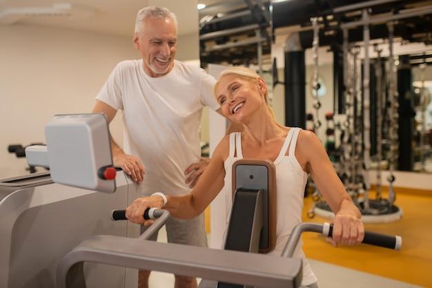 Пожилая пара вместе тренируется в тренажерном зале и прекрасно себя чувствует