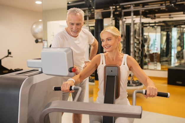 Пожилая пара вместе упражнениями в тренажерном зале и глядя на монитор