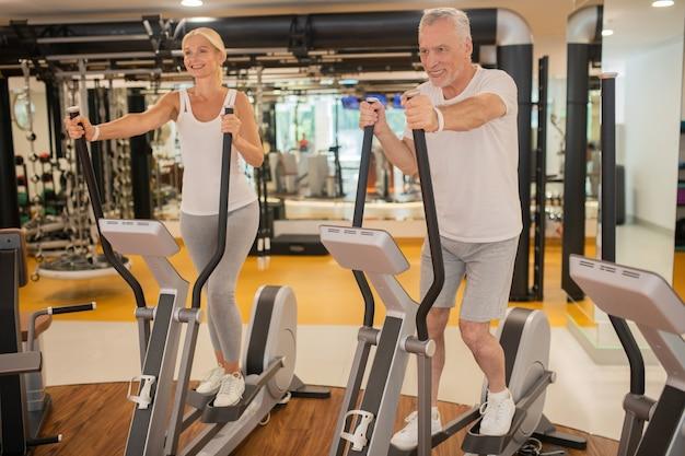 Пожилая пара тренируется вместе в тренажерном зале и выглядит решительно