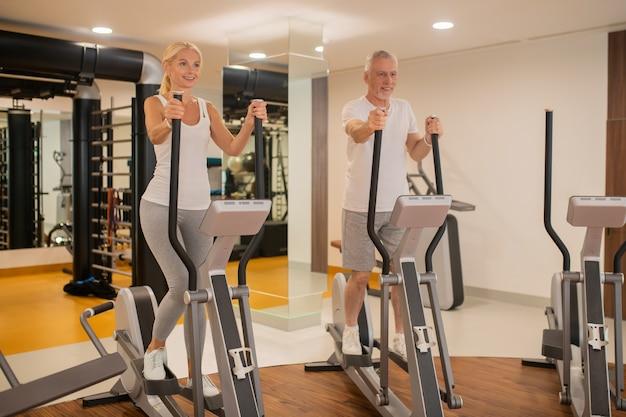 Пожилая пара тренируется вместе в тренажерном зале