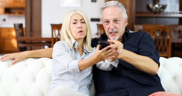 Mature couple fighting for remote control on a sofa