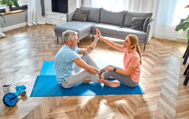 Пожилая пара дает пять жестов и делает упражнения дома и развлекается.