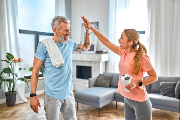 Пожилая пара дает пять жестов и делает упражнения дома и развлекается. Premium Фотографии