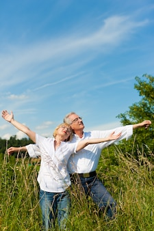 Mature couple having fun in a sunny meadow