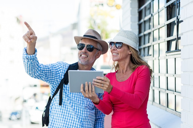 Mature couple holding digital tablet
