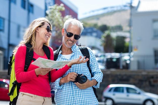 市内の地図とカメラを保持している成熟したカップル