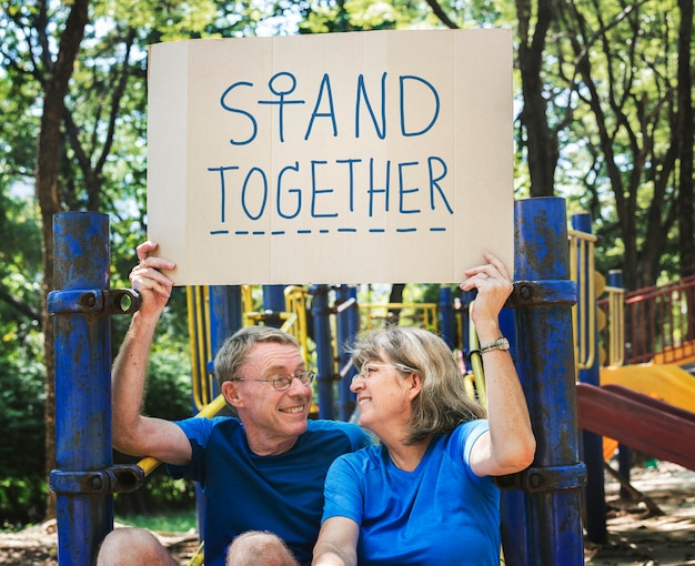 Mature couple holding a stand together signboard