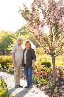 春の自然の中で外を抱いて成熟したカップル