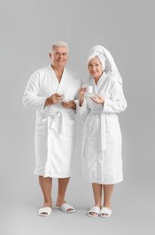 Пожилая пара в халатах пьет кофе