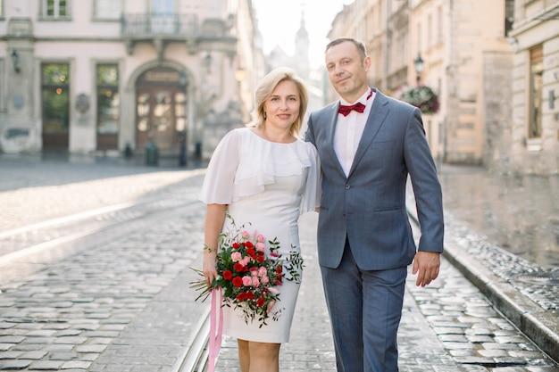 古いヨーロッパの街の通りを歩いて、エレガントでファッショナブルな服を着た成熟したカップル