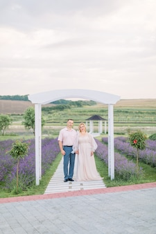 라벤더 밭에 있는 나무 아치 아래 야외에서 사랑에 빠진 성숙한 부부