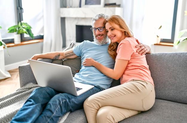 성숙한 부부는 노트북으로 집에서 소파에 앉아