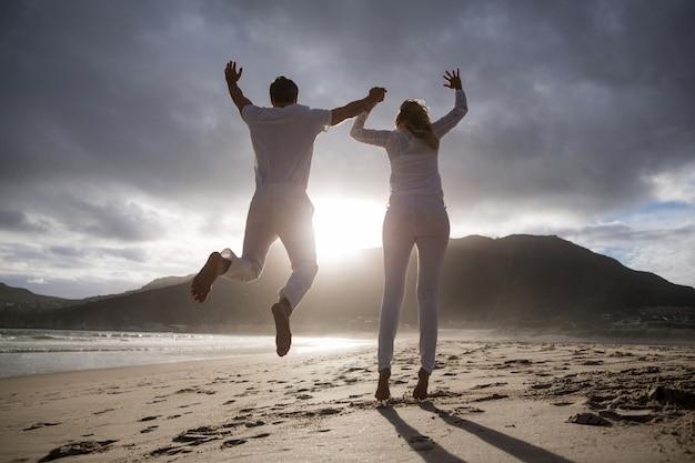 中高年カップルがビーチで空気中のジャンプ