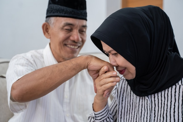 Пожилая пара целует руку мужа