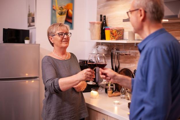 저녁에 레드 와인 잔을 들고 서로를 바라보는 성숙한 부부. 건강한 식사를 하는 동안 즐거운 대화를 나누는 사랑에 빠진 노부부.