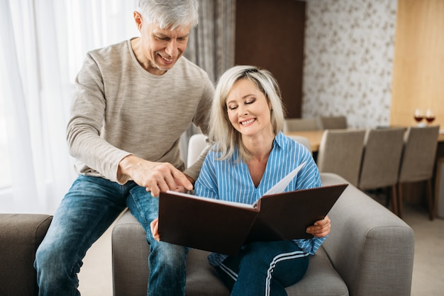 Mature couple looking at old photo album