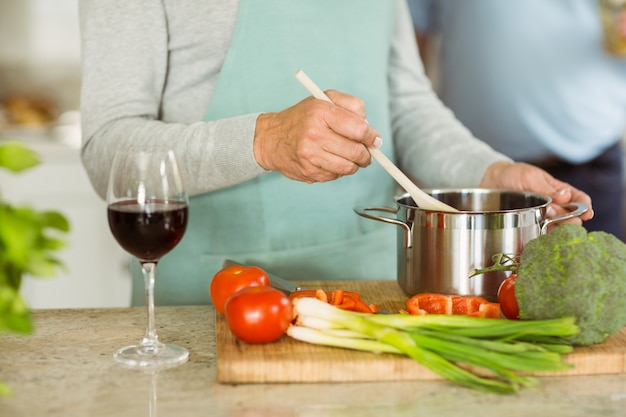 Mature couple making dinner together having red wine