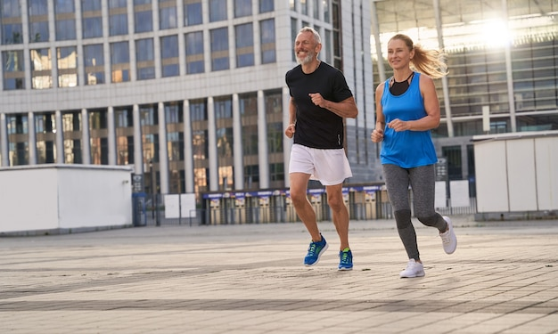 Mature couple man and woman exercising and jogging together in the city on a warm summer day