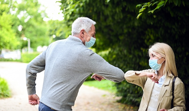 Пожилая пара встречается и приветствует себя локтем