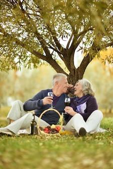 Пожилая пара на пикнике в осеннем парке