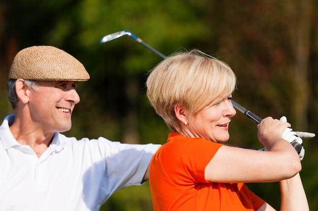 Mature couple playing golf