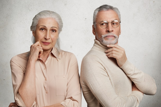 Пожилая пара позирует против белой бетонной стены
