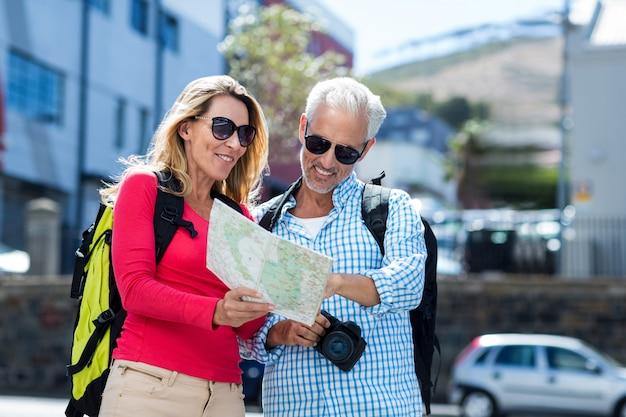 中高年カップルが市の地図を読む