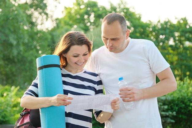 Пожилая пара, чтение бумажного документа письмо на открытом воздухе