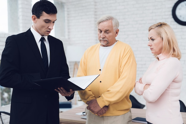 Mature couple at a reception with a lawyer.