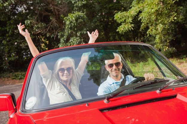 Mature couple in red cabriolet cheering at camera
