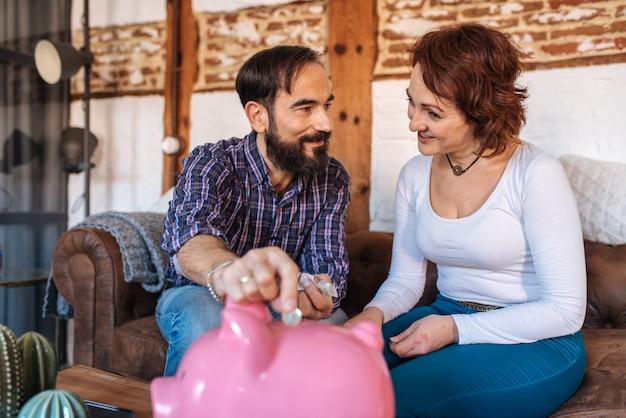 中高年カップルが自宅でソファでリラックスして貯金箱にお金を節約