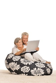 Mature couple relaxing at home with laptop on a white