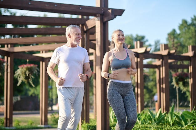 A mature couple running in the park and looking contented