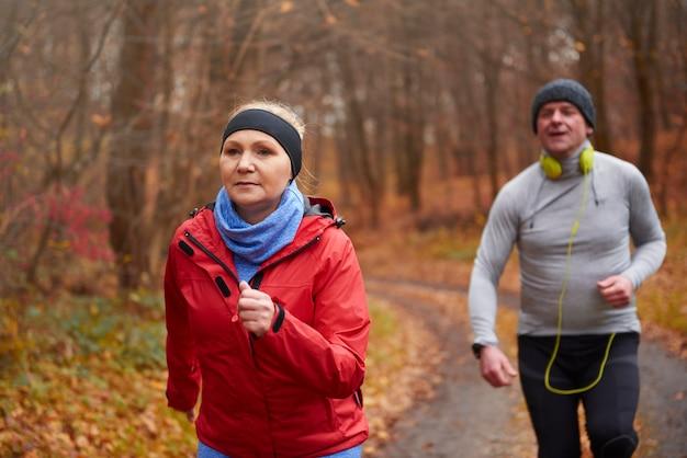 森の小道を走る成熟したカップル