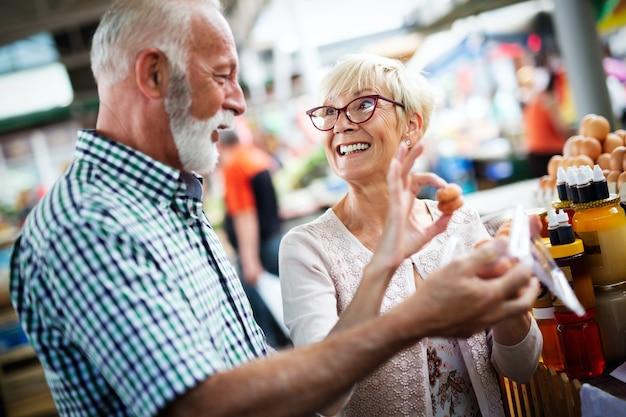 市場で野菜や果物を買い物する成熟したカップル。健康的なダイエット。