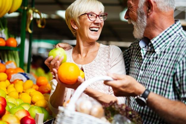 시장에서 야채와 과일을 쇼핑하는 성숙한 부부. 건강한 다이어트.
