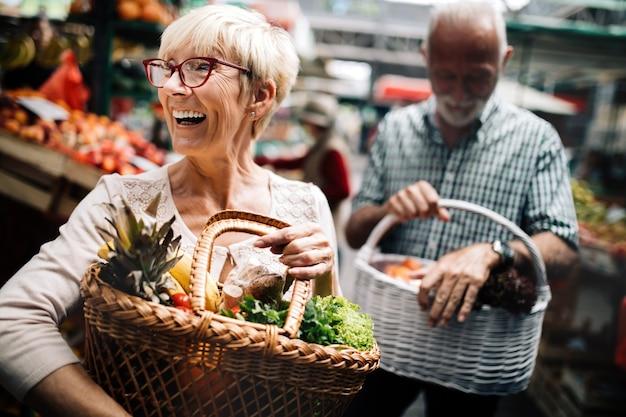 Пожилая пара, делая покупки овощей и фруктов на рынке. здоровая диета.
