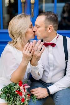 成熟したカップル、街の通りの青いヴィンテージのドアの前に座って、結婚指輪を見せて