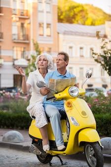 Пожилая пара, сидя на скутере.