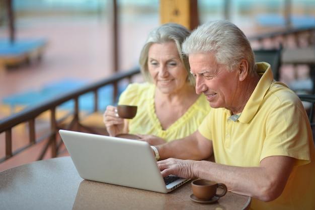 Пожилая пара сидит с ноутбуком в отеле