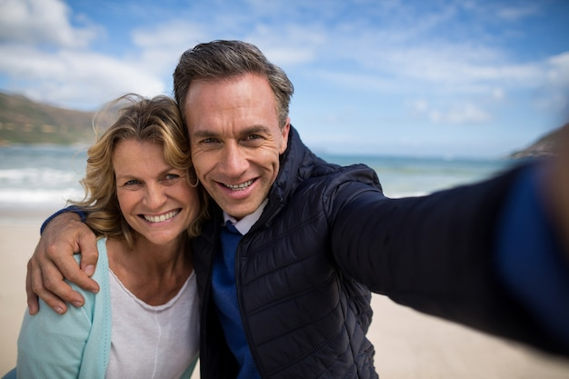 Mature couple smiling at camera on the beach