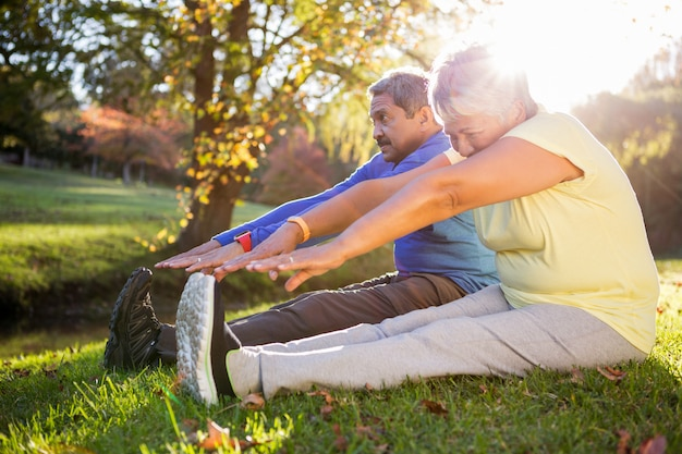 Mature couple stretching on field at park