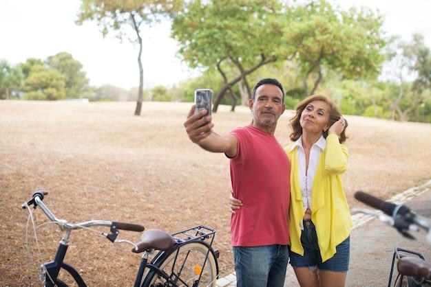 屋外の自転車で自分撮りをしている成熟したカップル